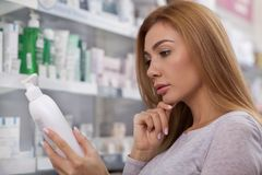 Gorgeous woman shopping at the drugstore. Close up of a beautiful woman rubbing her chin thoughtfully, reading label on a medication bottle at the pharmacy royalty free stock photo