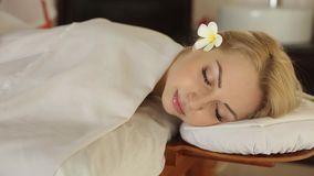 Close up of beautiful woman on spa bed at exotic resort. Pretty blonde girl relaxing and having massage with a flower in. Close up of beautiful woman on spa bed stock video