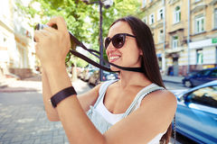 Close-up of beautiful woman taking a photo in old part of the c royalty free stock photography