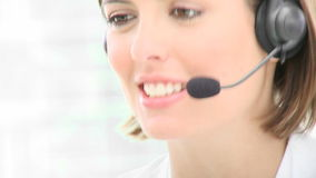 Close up of beautiful woman working in a call center. Close up of smiling beautiful woman working in a call center. Footage in high definition stock footage