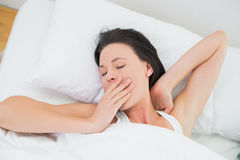 Close up of a beautiful woman yawning in bed Royalty Free Stock Photos