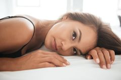 Close up of a beautiful young asian woman in sexy lingerie. Lying on her back and looking at camera on bed Royalty Free Stock Photography