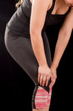 Close up of a beautiful young attractive sport woman holding injured knee suffering pain, in black background Stock Photos