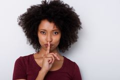 Close up beautiful young black woman with finger over lips gesturing silence. Close up portrait of beautiful young black woman with finger over lips gesturing Royalty Free Stock Photos