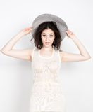 Close-up of beautiful young brunette woman holding a broad-brimmed hat, she expression of different emotions.  Royalty Free Stock Images