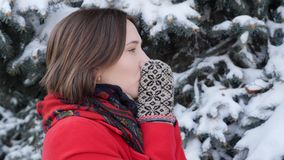 Close up Beautiful young brunette woman in red coat, scarf, mittens,  smiling freezing trying to warm up, blowing on hands outside. On winter snowy day stock video footage