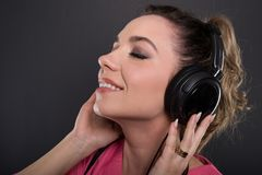 Close-up of beautiful young doctor listening to headphones Stock Image