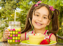 Close up of a beautiful young girl, preparing to eat a healthy fruit salad and a healthy drink in a garden background Stock Photography