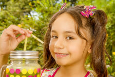 Close up of a beautiful young girl, preparing to eat a healthy fruit salad and a healthy drink in a garden background Stock Photo