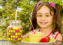 Close up of a beautiful young girl, preparing to eat a healthy fruit salad and a healthy drink in a garden background Stock Image