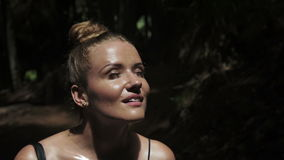 Close up of beautiful young girl standing over tropical nature. Beautiful happy young woman standing in the jungle scene, thinking while her eager eyes searches stock video