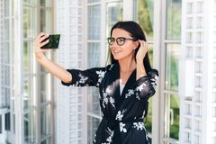 Close-up of a beautiful young girl wearing glasses has a European appearance, dark straight hair, wearing a silk outfit. Woman communicates with someone via stock photo