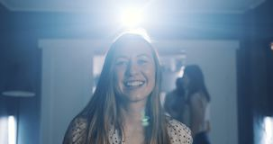 Close-up beautiful young happy European woman dancing, blowing on confetti and smiling at birthday party slow motion. Cheerful female student relaxing at fun stock footage