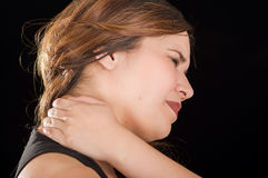 Close up of a beautiful young lady Suffer crick after workout in a black background Royalty Free Stock Photo