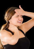 Close up of a beautiful young lady Suffer crick after workout with a hand in her forehead, in a black background Royalty Free Stock Photo