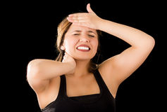 Close up of a beautiful young lady Suffer crick after workout with a hand in her forehead, in a black background Royalty Free Stock Photography