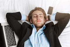 Close up of beautiful young manager in classy suit lying in bed with hands under head, fall asleep with laptop and. Smartphone after hard work Stock Photo