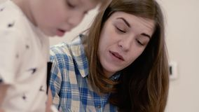 Charming woman and little boy doing homework. Close-up - beautiful young mother in plaid blue shirt smiles and says something to her little curious blurred son stock footage