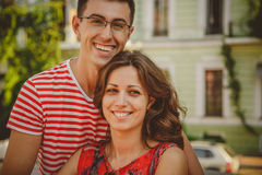 Close up of beautiful young smiling couple in love, hugging, standing behind each other outdoors at city street stock photography