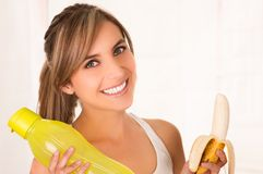 Close up of a beautiful young smiling woman wearing a white t-shirt and holding a yellow bottle of water and a banana in Stock Images