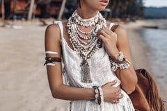 Close up of beautiful young stylish boho woman walking on the beach at sunset royalty free stock photo