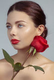 Close-up beautiful young woman with bright lipgloss makeup. Perfect clean skin, red lip make-up. Beautiful valentine visage w. Ith red rose flower. Romantic and stock photography