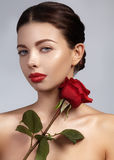 Close-up beautiful young woman with bright lipgloss makeup. Perfect clean skin, red lip make-up. Beautiful valentine visage w. Ith red rose flower. Romantic and royalty free stock photo