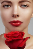 Close-up beautiful young woman with bright lipgloss makeup. Perfect clean skin, red lip make-up. Beautiful valentine visage w. Ith red rose flower. Romantic and royalty free stock images