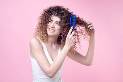 Close-up beautiful young woman combing her curl hair. On plain backgrond Royalty Free Stock Photos
