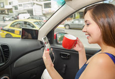 Close up of a beautiful young woman drinking a cup of coffe or tea and holding in her other hand a cellphone, while the Royalty Free Stock Image