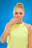 Close-up of a beautiful young woman with hand covering mouth. Royalty Free Stock Photo