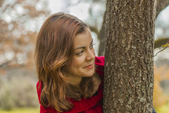 Close up beautiful young woman hiding behind a trunk of a tree. Nature autumn outdoors Royalty Free Stock Photography