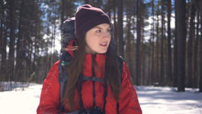 Close-up. Beautiful young woman hiking with a backpack in beautiful winter forest. stock video