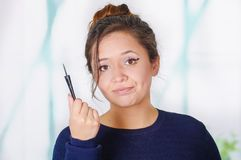 Close up of beautiful young woman holding a eyeliner in her hand, in a blurred background.  stock image
