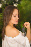 Close up of a beautiful young woman holding her keys and smiling in blurred background Royalty Free Stock Photos
