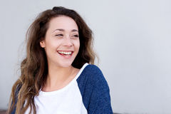 Close up beautiful young woman laughing by white background. Close up portrait of beautiful young woman laughing by white background Royalty Free Stock Photo
