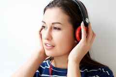 Close up beautiful young woman listening to music with headphones. Close up portrait of beautiful young woman listening to music with headphones Royalty Free Stock Image