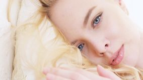 Close-up of beautiful young woman`s face with perfect makeup, blonde hair and blue-and-grey eyes lying on soft and white royalty free stock images
