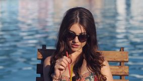 Close up Beautiful young woman wearing bikini drinking cocktail, sitting by the pool and sunbathing stock footage