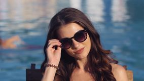 Close up Beautiful young woman wearing bikini drinking cocktail, sitting by the pool, sunbathing and wearing sunglasses stock video footage