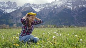Close up beautiful young woman weaves a wreath of meadow dandelion flowers and tries on herself on mountains background. 4k stock footage