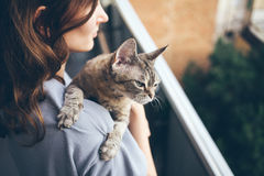 Close-up of beautiful young woman who is standing on a balcony with her cat. Royalty Free Stock Image