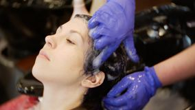 Close up. Hairdresser washes the client`s head, washing off the hair dye. Beauty concept. Cinematic view. Close up beauty concept. Hairdresser washes the client stock video