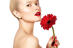 Close-up beauty photo sexy woman with red lips, lipstick and beautiful red flower. Spa clean skin Royalty Free Stock Photo