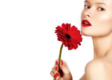 Close-up beauty photo sexy woman with red lips, lipstick and beautiful red flower. Spa clean skin Royalty Free Stock Photos