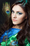 Close up beauty portrait of beautiful girl with peacock feather. Creative makeup peafowl feathers. Attractive mysterious Stock Photo