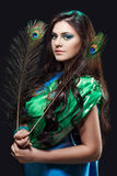 Close up beauty portrait of beautiful girl with peacock feather. Creative makeup peafowl feathers. Attractive mysterious Stock Photos