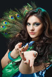 Close up beauty portrait of beautiful girl with peacock feather, lures, beckoning hands. Creative makeup peafowl royalty free stock image