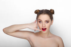 Close-up beauty portrait of young beautiful woman with clean fresh healthy skin funny bun hairdo doing a phone call sign with her Royalty Free Stock Photography