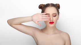 Close-up beauty portrait of young beautiful woman with clean fresh healthy skin funny bun hairdo howing her palm on white backgrou. Close-up beauty portrait of Stock Images